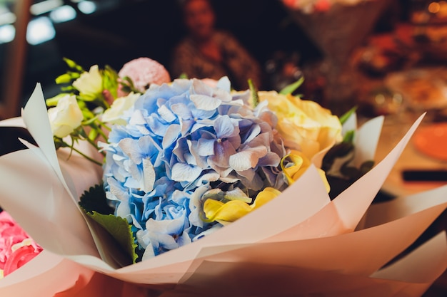Boeketten met bloemen op de vloer voor een bloemenwinkel met lelies, zonnebloemen, anjers, statices en meer. Premium Foto