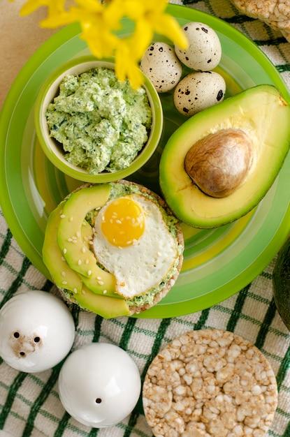 Boekweit knäckebröd met cottage cheese, spinazie, avocado en gebakken kwarteleitjes Premium Foto