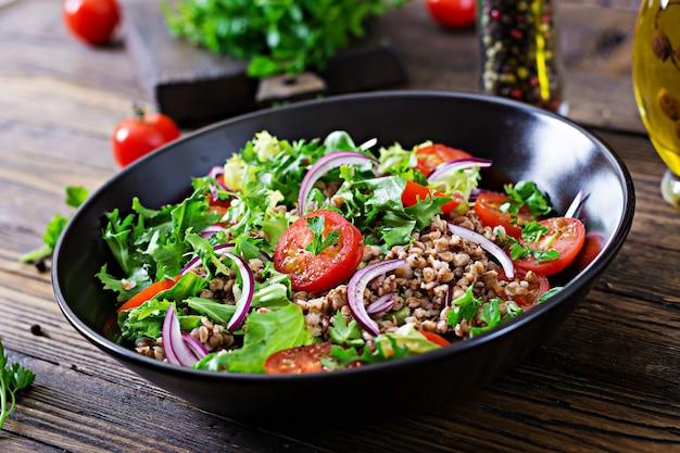 Boekweitsalade met kerstomaatjes, rode ui en verse kruiden. veganistisch eten. dieet menu. Gratis Foto