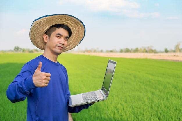 Boer man dragen hoed met behulp van laptopcomputer en duim op hand staande op groene rijst veld. Premium Foto