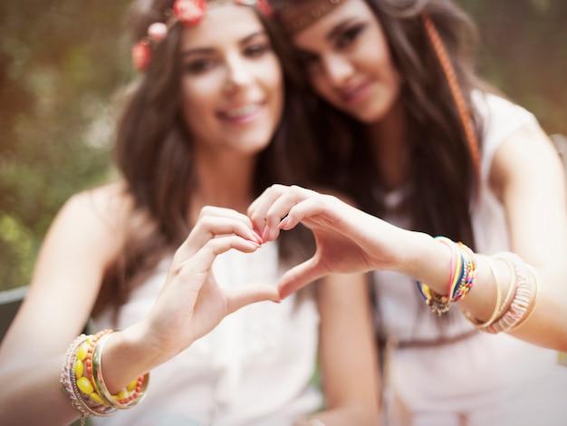 Boho-meisjes die hartvorm uit handen tonen Gratis Foto