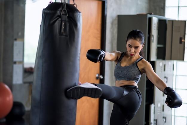 Boksen vrouw kick enorme bokszak in de sportschool Premium Foto