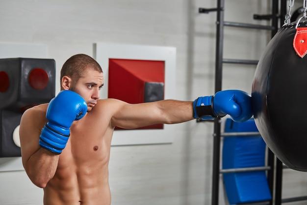 Bokser man tijdens het boksen zware tas raken op training fitness gym. naakte torso Premium Foto