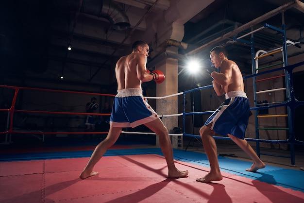 Boksers trainen kickboksen in de ring bij de gezondheidsclub Premium Foto