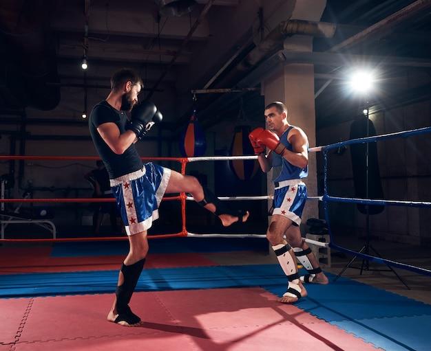 Boksers trainen kickboksen in de ring bij de healthclub Premium Foto