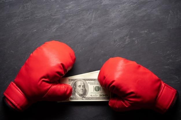 Bokshandschoenen houdt het dollarbankbiljet op zwarte cementachtergrond. Premium Foto