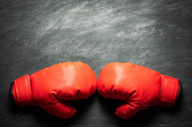 Bokshandschoenen op zwarte cementachtergrond. concept van vechten of boksen. Premium Foto