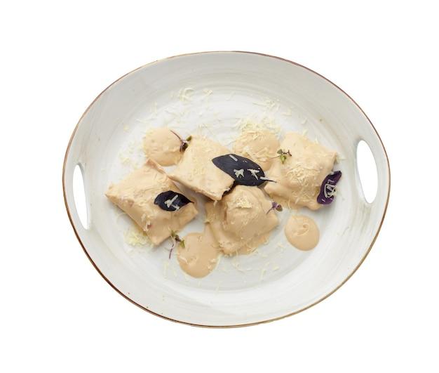 Bollen of vareniki met champignonsaus op wit wordt geïsoleerd Premium Foto