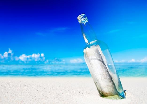 Boodschap in een fles op het strand. Gratis Foto