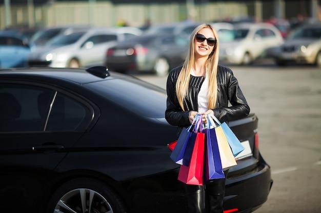 Boodschappen doen. de vrouwenholding kleurde zakken dichtbij haar auto in zwarte vrijdagvakantie Premium Foto