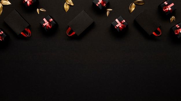 Boodschappentassen en gouden bladeren op zwarte achtergrond Gratis Foto