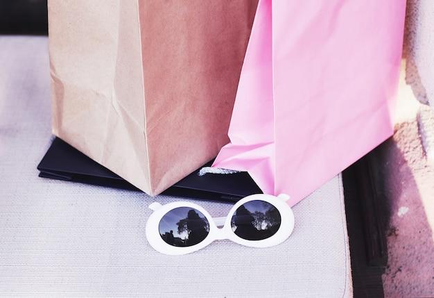 Boodschappentassen en witte zonnebril. levensstijl van jonge vrouwen. Gratis Foto