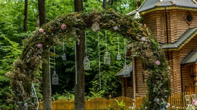Boog voor de huwelijksceremonie. versierd met stoffen bloemen en groen. is gelegen in een dennenbos. achtergrond kerk. bruiloft decoraties in rustieke stijl. pas getrouwd. bruiloft decor. Premium Foto