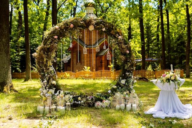 Boog voor de huwelijksceremonie. versierd met stoffen bloemen en groen. ligt in een dennenbos. Premium Foto