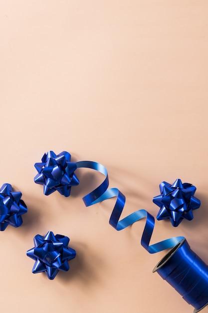 Boog voor jubileumdecoratie op koraalkleurige achtergrond. positie voor verjaardag, moederdag of bruiloft. glanzend satijn decoratie cadeau aanwezig, vakantie ontwerp Premium Foto