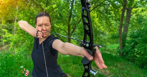 Boogschieten, jonge vrouw met een pijl in een boog gericht op het raken van een doelwit Premium Foto