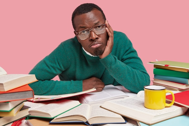 Boos donkere man heeft een verveelde uitdrukking, houdt de handen op de wang, draagt een bril en een groene trui, omringd met veel boeken Gratis Foto