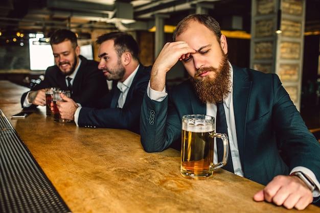 Boos en moe jonge man zit t bar. hij kijkt naar beneden en houdt zijn hand op het voorhoofd. mok bier staan op toog. andere twee jonge mannen zitten achter. Premium Foto