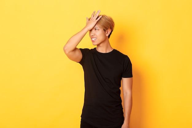 Boos en onrustige aziatische man breekt vergeetachtig voorhoofd, staande over gele muur Gratis Foto