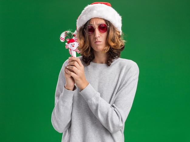 Boos jonge man met kerst kerstmuts en rode bril bedrijf kerst candy cane camera kijken met droevige uitdrukking staande over groene achtergrond Gratis Foto