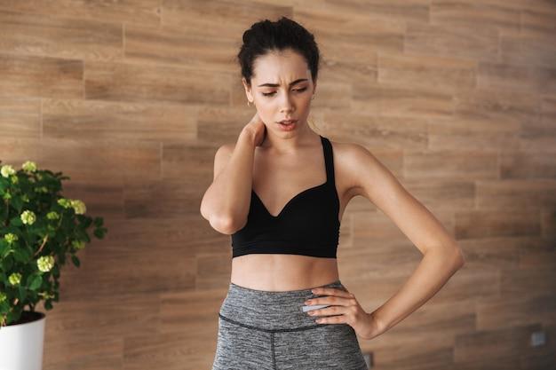 Boos jonge sportvrouw die lijdt aan nekpijn Premium Foto