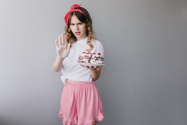 Boos vrouw in roze rok poseren met verjaardagstaart. stijlvol meisje met taart geïsoleerd. Gratis Foto