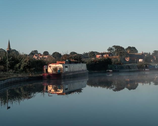 Boot op het water vlakbij de kust met gebouwen in de verte onder een blauwe lucht Gratis Foto
