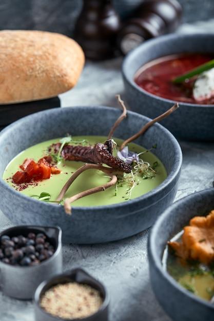 Bord met aspergesoep met octopus, een bord met traditionele borsjt met zure room, een bord met champignonsoep Premium Foto