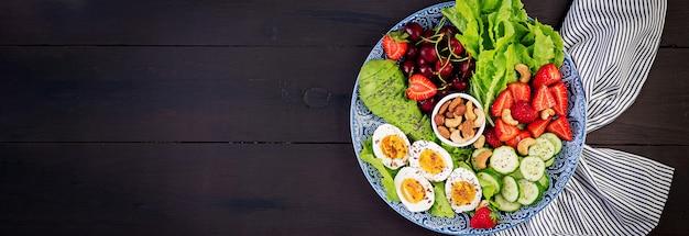 Bord met een paleo dieetvoeding. gekookte eieren, avocado, komkommer, noten, kersen en aardbeien. paleo ontbijt. bovenaanzicht Gratis Foto