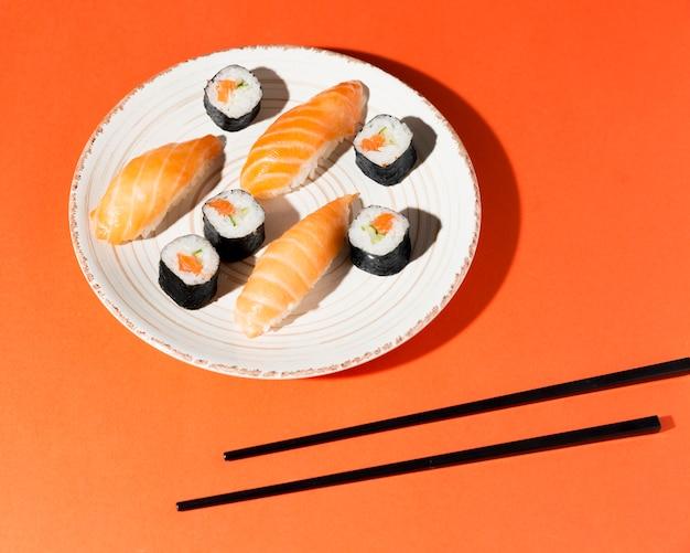 Bord met heerlijke variëteit aan sushi en eetstokjes Gratis Foto