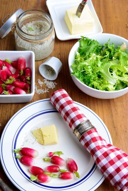 Bord met radijs, boter en salade op een rustieke tafel Premium Foto