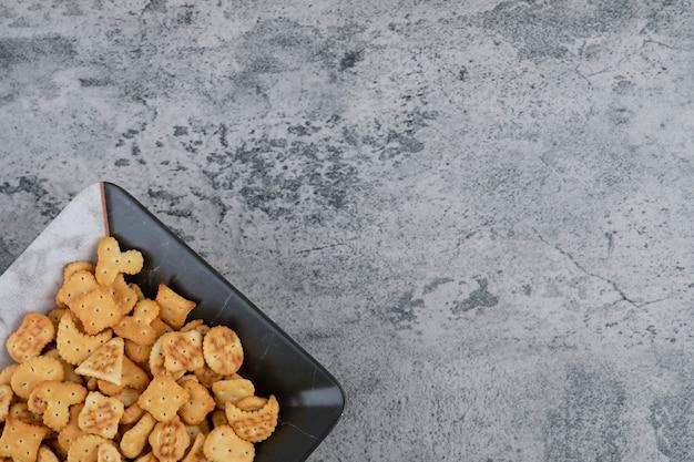 Bord vol met droge gezouten crackers op marmeren achtergrond. Gratis Foto