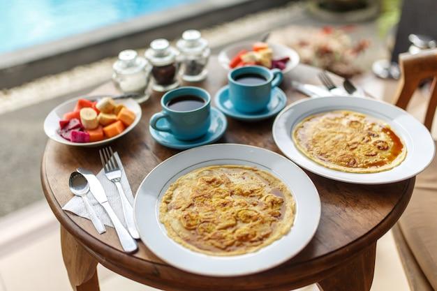 Borden met bananenpannenkoeken, tropisch fruit en twee kopjes koffie op houten tafel. Premium Foto