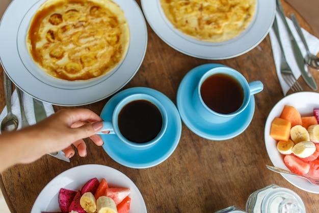 Borden met bananenpannenkoeken, tropisch fruit en twee kopjes koffie op houten tafel, Premium Foto