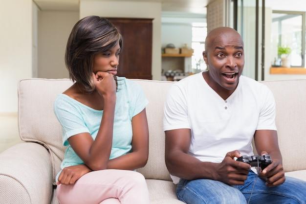 Bored vrouwenzitting naast haar vriend het spelen videospelletjes Premium Foto