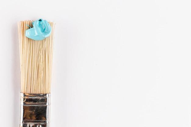 Borstel met blauwe verf en witte achtergrond Gratis Foto