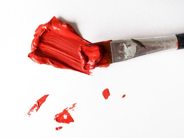Borstel met rode verf op canvas Gratis Foto