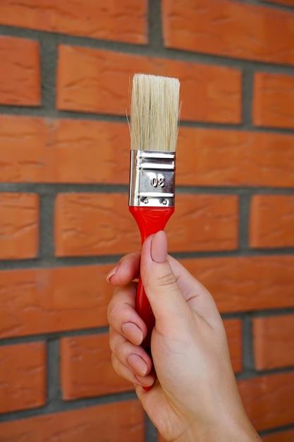 Borstel voor het schilderen van de muren in de meisjeshand op een muur van tegenoverliggende rode baksteen Premium Foto