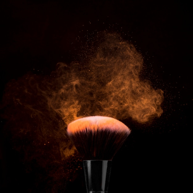 Borstel voor make-up in poeder burst op donkere achtergrond Gratis Foto