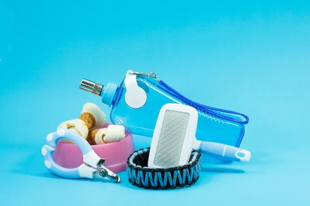 Borstelkam, kom met snacks, kragen, nagelschaartje en waterflessen op blauwe achtergrond Premium Foto