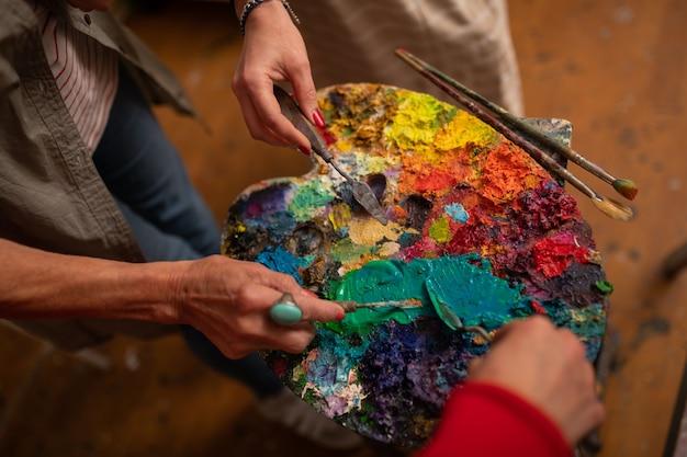 Borstels dichtbij palet. bovenaanzicht van drie vrouwelijke kunstenaars die hun penselen in de buurt van het kleurenpalet houden Premium Foto