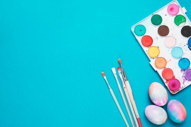 Borstels; geschilderde paaseieren en plastic palet met waterkleur op blauwe achtergrond Gratis Foto