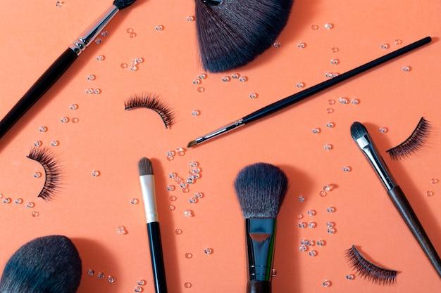 Borstels voor make-up van verschillende groottes op een pasteloranje Premium Foto