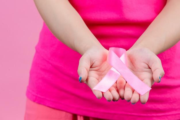 Borstkanker bewustzijn, roze lint geplaatst op beide handvrouwen is een symbool voor wereldborstkanker dag. Gratis Foto
