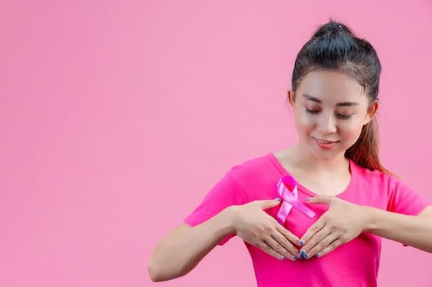 Borstkanker bewustzijn, vrouw in roze t-shirt met satijn roze lint op haar borst, ter ondersteuning van symbool borstkanker bewustzijn Gratis Foto