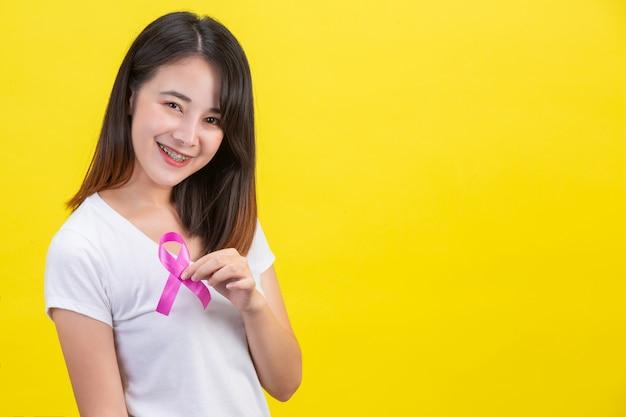 Borstkanker, een vrouw in een wit t-shirt met een satijnen roze lint op haar borst, een symbool voor bewustzijn van borstkanker Gratis Foto