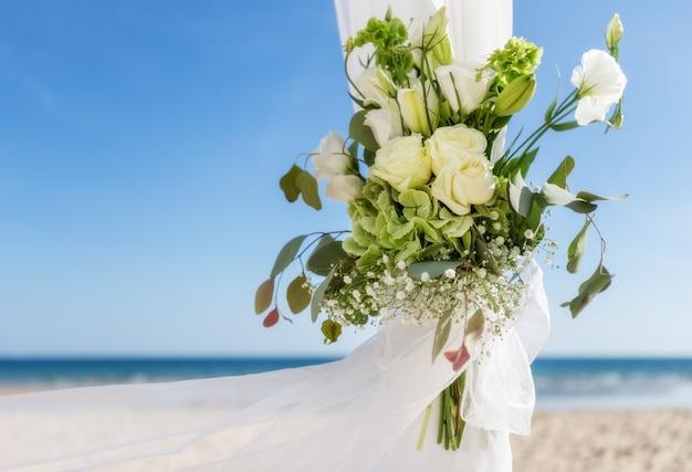 Bos bloemen in een vaas voor huwelijksceremonie. op de achtergrond de zee. Premium Foto