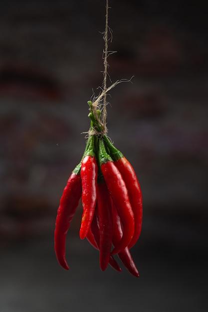 Bos van gedroogde roodgloeiende chili peper op zwart. Gratis Foto