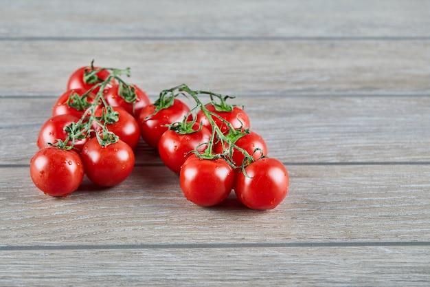 Bos van rode tomaten met tak op houten lijst Gratis Foto