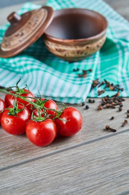 Bos van tomaten met tak en lege kom met kruidnagel op houten lijst Gratis Foto